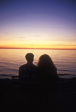 Boy and girl watching sunset, Visby, Gotland, Sweden *** Local Caption ***