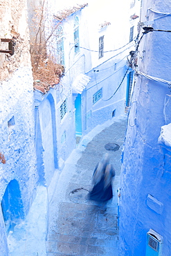 Woman in dark blue traditional clothing running down (blurred) a typical blue painted alleyway in Chefchaouen, Morocco, North Africa, Africa