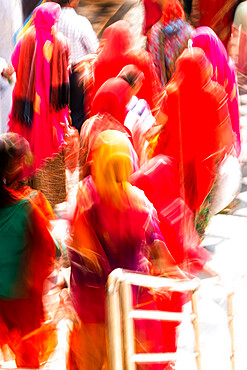 Brightly coloured saris (clothing) and veils, blurred in motion for effect, worn by women walking down towards the sacred lake, Pushkar, Rajasthan, India, Asia