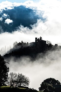 Silhouetted village of Montefioralle in early morning mist as sun breaks through, Tuscany, Italy