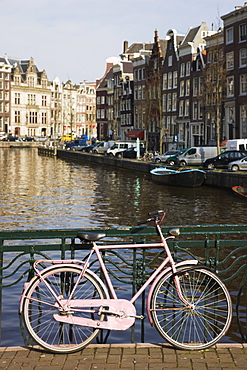 Old pink bicycle by the Herengracht canal, Amsterdam, Netherlands, Europe