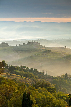 Early morning view across misty hills from San Gimignano, Tuscany, Italy, Europe