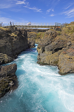 Tourists on bridge over Barnafoss, a series of rapids on the Hvita river, a glacial river from Langjokull, West area, Iceland, Polar Regions