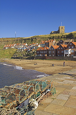 Whitby church, sandy beach and lobster pots on quayside, Whitby, North Yorkshire, Yorkshire, England, United Kingdom, Europe