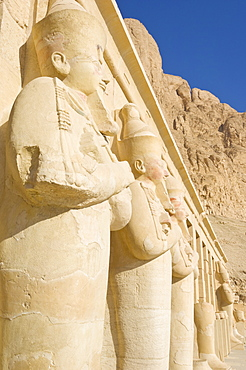 Restored Osirid statues of the female pharaoh Hatshepsut on the pillars of the portico entrance to the third terrace of theTemple of Hatshepsut, Deir el Bahari, West bank of the River Nile, Thebes, UNESCO World Heritage Site, Egypt, North Africa, Africa