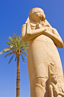 Statue of the great pharaoh Rameses II with small statue of his daughter Bent'anta between his legs in the forecourt behind the first Pylon of the great Temple at Karnak, near  Luxor, Thebes, UNESCO World Heritage Site, Egypt, North Africa, Africa