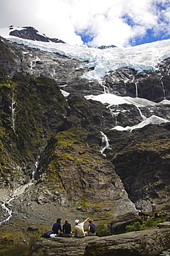 Hikers watch water cascading off Rob Roy Glacier in Mount Aspiring National Park, South Island, New Zealand, Pacific