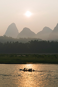 Tourist boat sailing through karst scenery at sunrise on the Li river (Lijiang) in Yangshuo, near Guilin, Guangxi Province, China, Asia