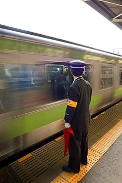 Platform conductor, subway train at rush hour, Shinjuku, Tokyo, Honshu, Japan, Asia