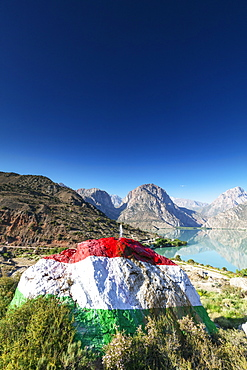Iskanderkul Lake with a large rock painted in the colours of the Tajikistan flag in the foreground, Fan Mountains, Tajikistan, Central Asia, Asia