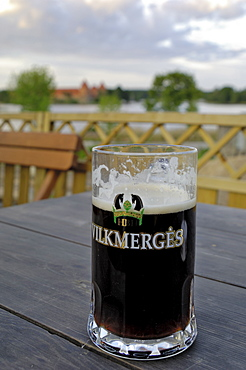 Vilkmerges, Lithuanian dark beer, with Trakai Castle in the background, Lithuania, Baltic States, Europe