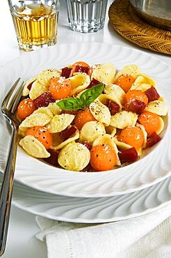 Orecchiette pasta with melon ball, prosciutto (ham), parmesan cheese and basil, Italy, Europe