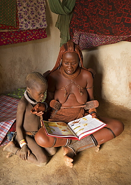 Himba woman and child reading, Kaokoland, Namibia, Africa