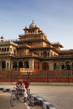Rickshaw rider resting outside the ornate Albert Hall museum in the city of Jaipur, Rajasthan, India, Asia