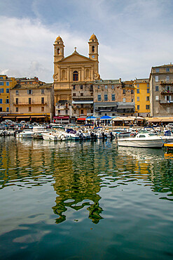 Boats moored in the port at Bastia with St Jean Baptiste church