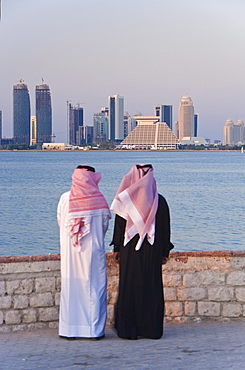 Two men wearing traditional dress of thobe and gutra (headdress) looking across Doha Bay from the Corniche to the new city skyline and West Bay business and financial district, Doha, Qatar, Middle East