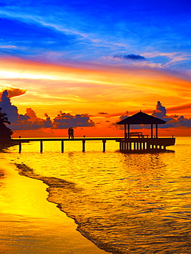Couple on jetty looking at sunset, The Maldives, Indian Ocean, Asia