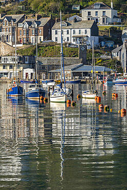 Boats moored in Looe???s pretty harbour at dawn, Looe, Cornwall, England. Spring (April) 2021