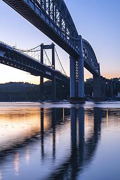 Dawn sky behind Brunel???s Royal Albert Bridge and the Tamar Bridge, Saltash, Cornwall, England. Spring (April) 2021.