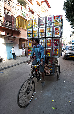Piled up empty oil tins, being carried by cycle rickshaw to be recycled and used for slum house walls, Kolkata (Calcutta), West Bengal, India, Asia