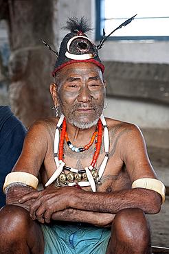Naga head hunter, Wokshing Pensha, wearing Naga tribal necklaces and hat, and chest tattoo marking him as having taken a head, Nagaland, India, Asia