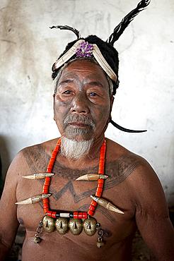 Naga man, Nokphong Wangpen, head hunter, with chest tattoo marking him as having taken a head, and Naga necklace, Nagaland, India, Asia