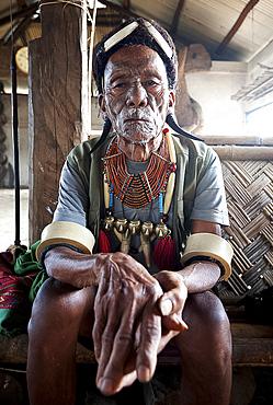 Gangchung Wangben, Naga man, headhunter, wearing horn earrings, Naga necklaces with brass heads and elephant tusk arm bands, Nagaland, India, Asia