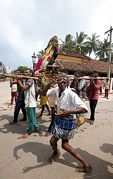 Men dancing to drumbeat as bronze deity covered with puja mala (garlands) being carried along the street, Tranquebar, Tamil Nadu, India, Asia