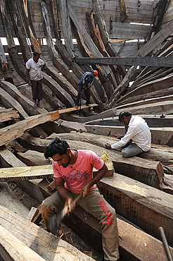 Carpenters working to build an ocean going wooden dhow entirely by hand, Mandvi shipyard, Gujarat, India, Asia