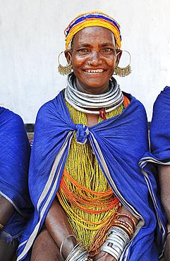 Smiling Bonda tribeswoman wearing traditional beads and earrings, with shaven head and blue shawl, Onukadelli, Odisha, India, Asia