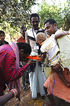 Mali tribesman offering puja gift to temple pundit after shaving his child's head at the festival of Shivraatri, Koraput, Odisha, India, Asia