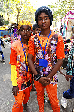 Two young pilgrims, in orange T shirts with images of Lord Shiva, going to Gupteswar cave Shiva shrine, Jeypore, Odisha, India, Asia