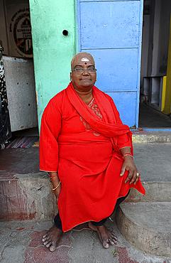 Woman with shaved head, Shiva devotee, dressed in red, outside 11th century Brihadisvara Cholan temple, Thanjavur, Tamil Nadu, India, Asia
