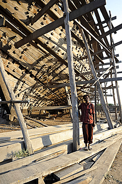 Boatbuilder beneath the hull of ocean going dhow under construction by hand from Sal wood, Rukmavati River, Mandvi, Gujarat, India, Asia