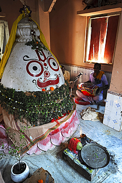 Musician plays the drum at the shrine to Lord Jagannath inside the village temple, rural Odisha, India, Asia