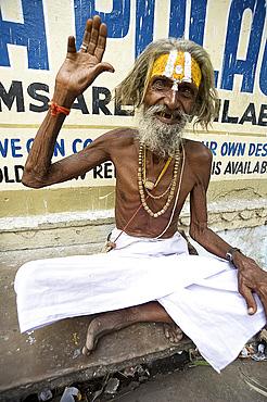 Holy man (Saddhu) with red cotton rolimoli on wrist and tilak mark on forehead denoting devotion to Hindu god Vishnu, Udaipur, Rajasthan, India, Asia