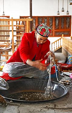Uyghur woman spinning silk thread from cocoons in traditional silk workshop, Jiya, Xinjiang, China, Asia