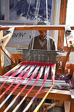 Uyghur man at loom weaving tie dyed silk thread into traditional cloth, Jiya, Xinjiang, China, Asia
