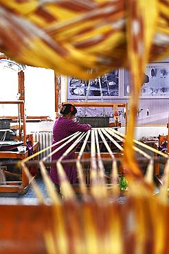 Uyghur woman preparing loom with tie dyed silk thread ready for weaving, Jiya, Xinjiang, China, Asia