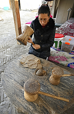 Uyghur woman beating boiled Mulberry bark with wooden mallet for paper making, Hotan, China, Asia