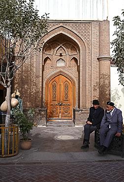 Two Uyghur Muslim men sitting outside city centre mosque, Kashgar, Xinjiang, China, Asia
