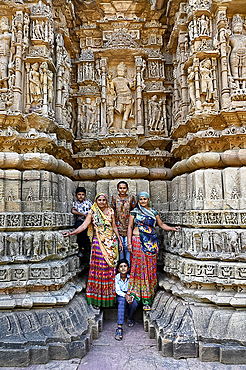 Family posing for photograph at the ornately carved Modhera Sun temple, built in 1026, Modhera, Mehsana, Gujarat, India, Asia