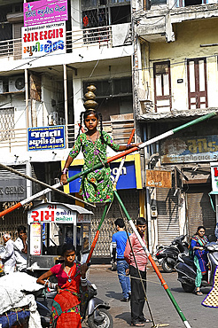 Young girl performing on a tightrope erected in a busy street to earn money, old Ahmedabad, Gujarat, India, Asia