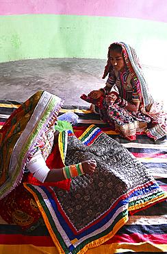 Women embroidering traditional tribal quilts in their bhunga (circular village mud house), Bhirindiara, Kutch, Gujarat, India, Asia