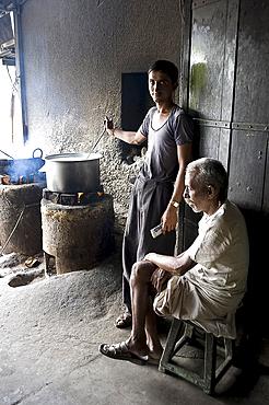 Young man stirring milk for chai, with blind man sitting beside him, roadside chai stall, Dangiyawas, Rajasthan, India, Asia