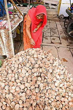 Woman in red sari with pile of terracotta deepak candle dishes for Diwali festival celebrations, Jodhpur, Rajasthan, India, Asia