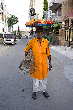 Man in yellow kurta with tray of snacks on his head and table under his arm, to sell in the market, Jodhpur, Rajasthan, India, Asia