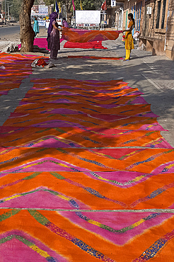 Women laying newly printed dupattas out to dry in the street, Jodhpur, Rajasthan, India, Asia