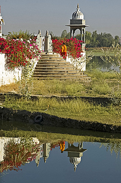 Reflection of monk entering the lake temple for puja at dawn, Dungarpur, Rajasthan, India, Asia