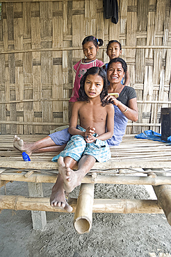 Mishing tribeswoman combing her daughter's hair on the verandah of their family home, Majuli Island, Assam, India, Asia